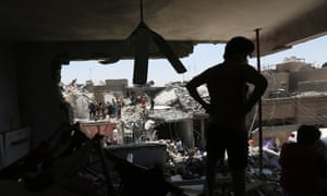 People stand in rubble after a bombing in the eastern neighborhood of New Baghdad on July 6, 2015. At least a dozen civilians were killed on when a Russian-made fighter jet accidentally dropped a bomb over a Baghdad neighborhood.