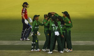 Diana Baig (centre) of Pakistan celebrates with teammates after claiming the early wicket of Amy Jones.