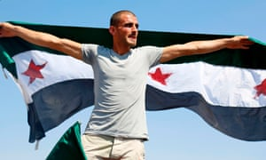 A Syrian man waves a flag of the opposition as he protests against the Assad regime and Russia in the rebel-held town of Maaret al-Numan in the north of Idlib province.