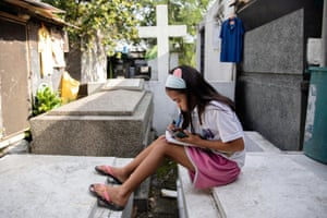 Grade 5 student Lovely Joy de Castro, 11, who lives at a makeshift home in a cemetery in Makati City, sometimes studies sitting on gravestones to avoid getting under the feet of her family cooking chicken to sell to visitors