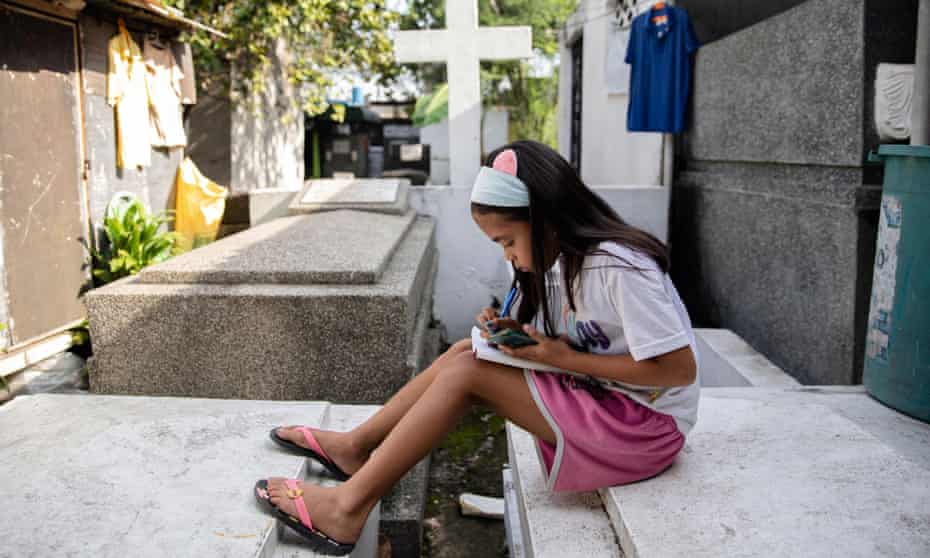Lovely Joy de Castro, 11, takes part in at an online class in the Manila cemetery where her family lives.