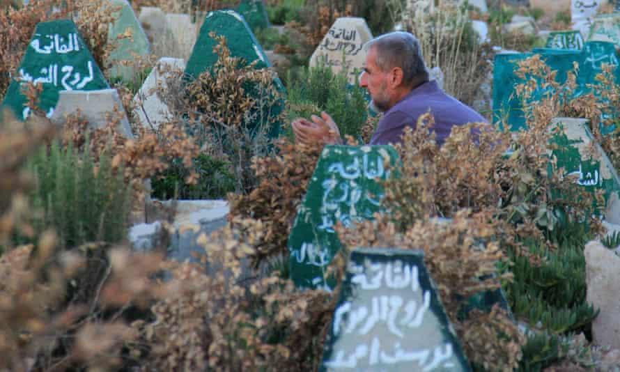 رجل يصلي في مقبرة في محافظة إدلب السورية ، في عام 2017 ، بعد هجوم بالغاز السام يُعتقد أنه قتل 89 شخصًا.