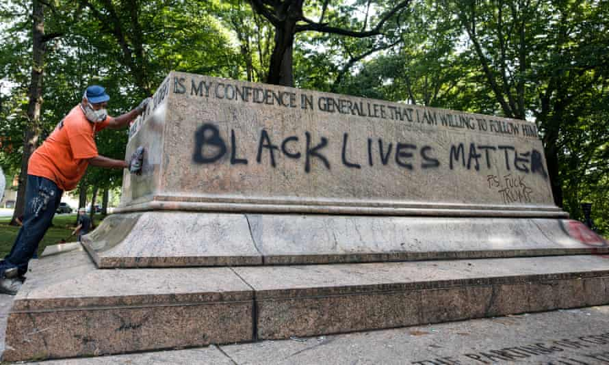 A city worker removes graffiti from the base of what was once the Jackson-Lee Monument, a Confederate statue removed from Wyman Park, Baltimore on 16 August 2017