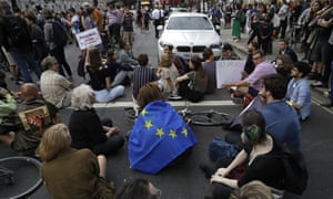 Anti-Brexit supporters sit in the road opposite the Houses of Parliament in London.