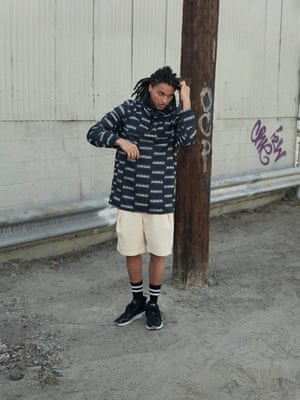 black neck warmer Columbia from Urban Outfitters, black and white logo design jacket from Napapijri, cream knee length shorts Cedric Charlier, Far Fetch, black ankle socks with white stripes, Topman, black and grey trainers with white sole, Adidas