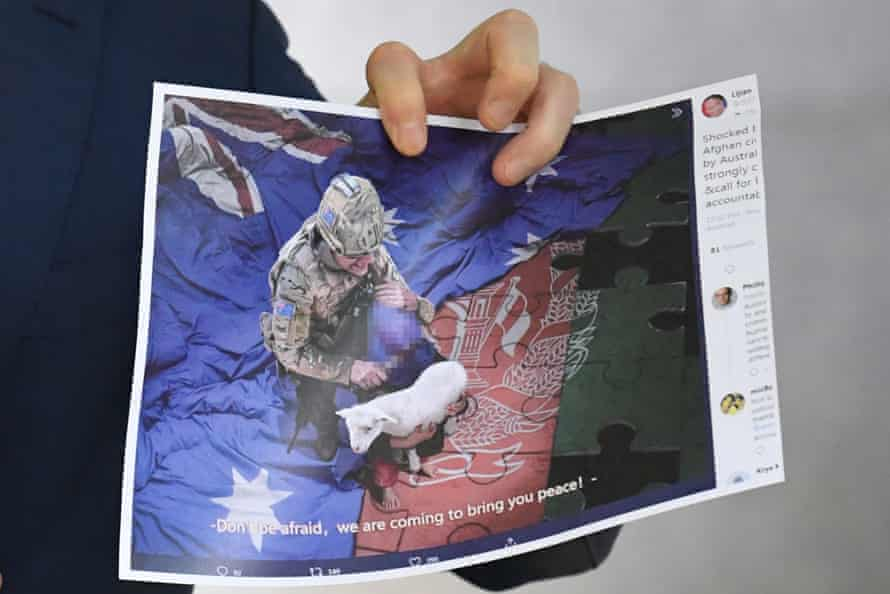A journalist holds a copy of the image released by China's foreign ministry showing an Australian soldier. This photograph has been pixellated by the Guardian.