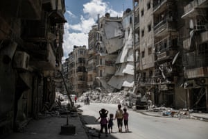 Children walk towards a building that was destroyed by a barrel bomb in the Sha'ar neighbourhood of Aleppo, Syria, on 3 June 2014