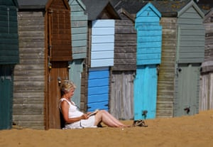 A lady reads a book in the afternoon sunshine on the beach in Broadstairs, Kent