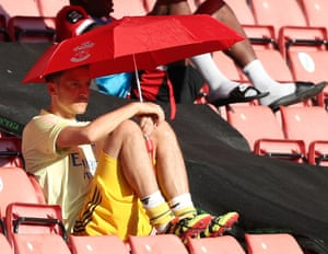 Mesut Ozil shelters from the sun under a Southampton umbrella.