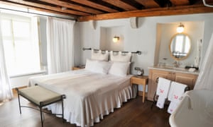 A room in the Three Sisters hotel: wooden floor, double bed with a white cover, large window and the edge of a bath with a curtain around it