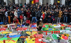 People gather at Place de la Bourse in Brussels to commemorate the attacks of 22 March 2016