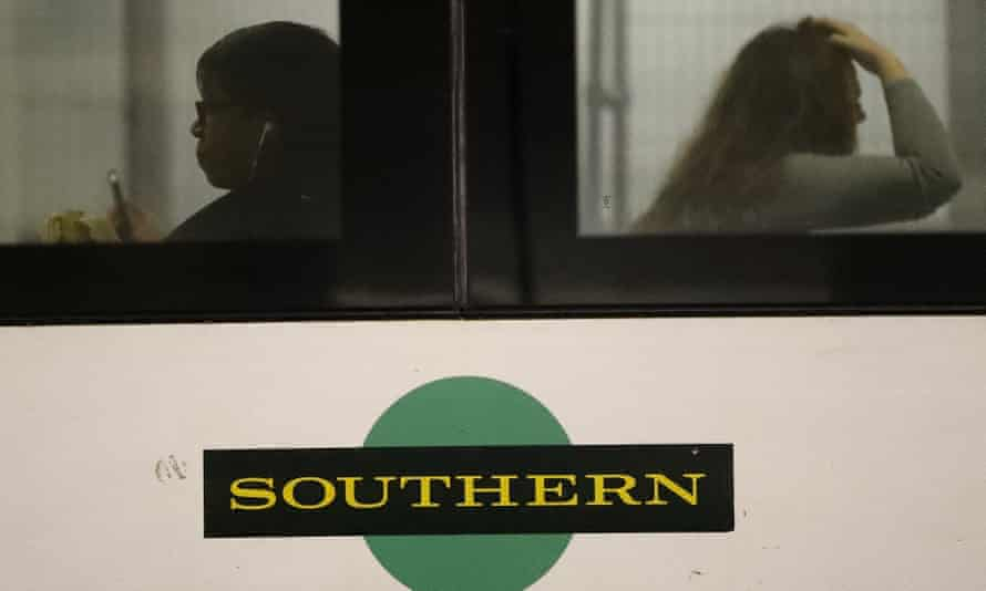 People sit inside a Southern train at Victoria Station in London.