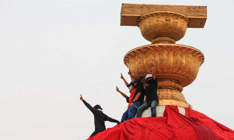 Protesters show the three-finger salute atop the Democracy Monument in Bangkok