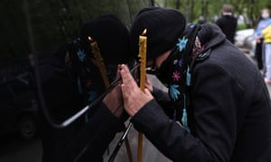 Orthodox deacon Andrei Molchanov's funeral, who died after contracting the coronavirus disease (COVID-19), in MoscowA woman mourns next to a funeral service vehicle transporting the coffin of Orthodox deacon Andrei Molchanov, 54, who died after contracting the coronavirus disease (COVID-19), near a church, where Molchanov served as a clergyman, in Moscow, Russia May 9, 2020. REUTERS/Evgenia Novozhenina