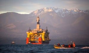 In this April 17, 2015 file photo, with the Olympic Mountains in the background, a small boat crosses in front of the Transocean Polar Pioneer, a semi-submersible drilling unit that Royal Dutch Shell leases from Transocean Ltd., as it arrives in Port Angeles, Wash., aboard a transport ship after traveling across the Pacific before its eventual Arctic destination. The U.S. government on Monday gave Shell the final permit it needs to drill for oil in the Arctic Ocean off Alaska's northwest coast for the first time in more than two decades.  (Daniella Beccaria/seattlepi.com via AP, File) MAGS OUT; NO SALES; SEATTLE TIMES OUT; TV OUT; MANDATORY CREDIT