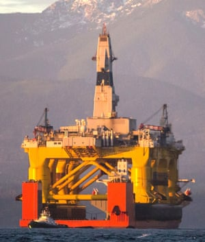 FILE - In this April 17, 2015 file photo, with the Olympic Mountains in the background, a small boat crosses in front of the Transocean Polar Pioneer, a semi-submersible drilling unit that Royal Dutch Shell leases from Transocean Ltd., as it arrives in Port Angeles, Wash., aboard a transport ship after traveling across the Pacific before its eventual Arctic destination.