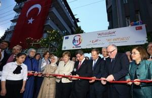 Turkish Prime Minister Ahmet Davutoğlu and German Chancellor Angela Merkel and other ministers and officials cut a ribbon during the opening ceremony of a Child Services Center for Syrian refugees in Gaziantep, Turkey