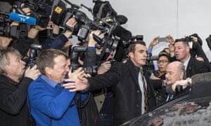 A media scrum surrounds Blatter.
