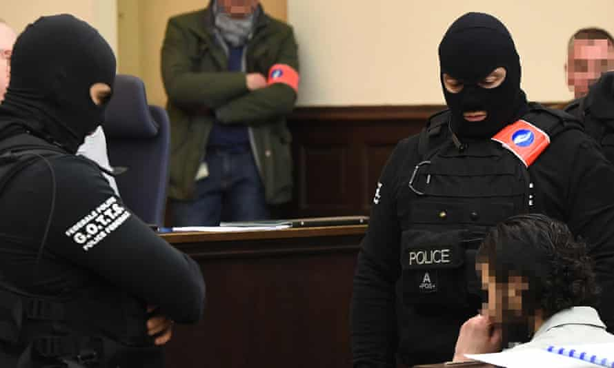 Salah Abdeslam sits in court surrounded by Belgian police officers