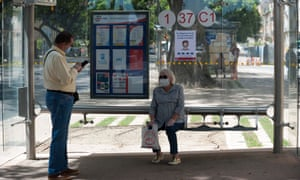 A woman wearing a face mask sits at a bus stop during the national lockdown amid coronavirus crisis.