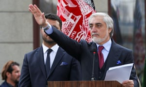 Abdullah Abdullah waves to supporters during a swearing-in ceremony in Kabul.