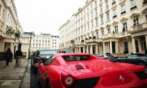 Pedestrians pass a red Ferrari parked outside properties in Kensington, London