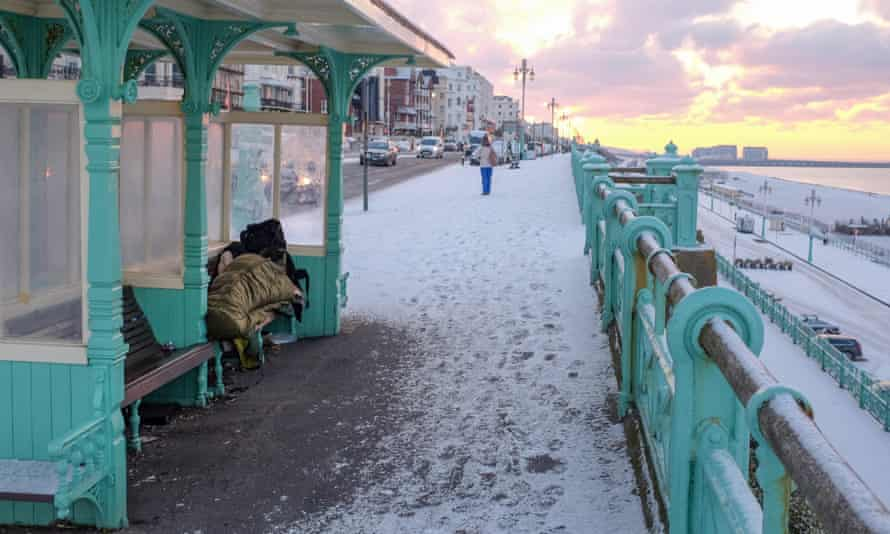 A homeless person tries to stay warm in a shelter on Brighton seafront in freezing conditions
