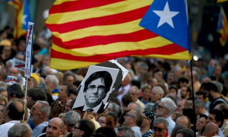 Protesters hold Catalan flags and a picture of the ousted former president Carles Puigdemont at a rally in Barcelona