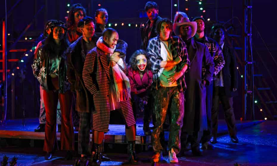 woman in clown make up stands in centre of group onstage