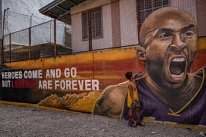 A child stands next to a Kobe Bryant mural outside the 'House of Kobe' basketball court in Valenzuela, Manila.