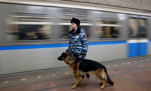 A Russian police officer on patrol with a dog at the metro station in Moscow amid tightened security following the attack.