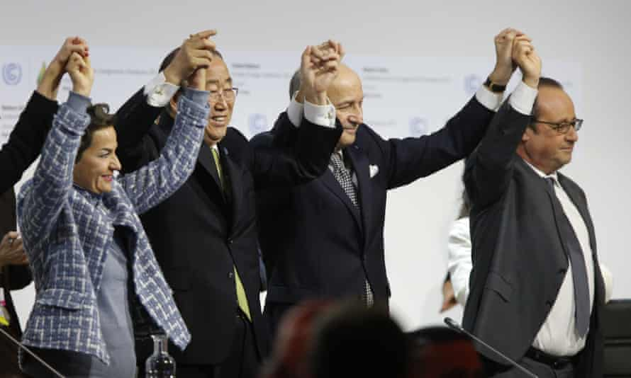 French foreign minister and president-designate of COP21 Laurent Fabius (centre), raises hands with UN secretary general Ban Ki Moon and French president François Hollande.