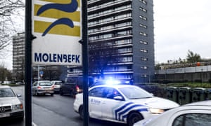A road sign in the Molenbeek district in Brussels with a police car passing behind