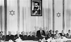 The first Israeli prime minister, David Ben-Gurion, standing under a portrait of Theodor Herzl, officially proclaims the state of Israel on 14 May 1948 in Tel Aviv.