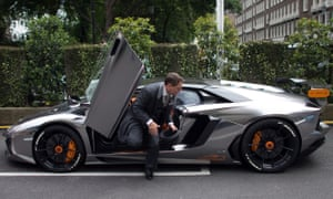 A valet climbs out of a Lamborghini Aventador