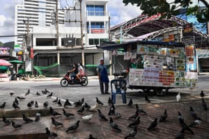 A food vendor waits for customers in front of empty shop houses along Patong beach in Phuket, which has seen a lack of tourists due to ongoing restrictions relating to the COVID-19 novel coronavirus. -