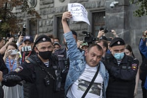 Police detain a supporter of Alexei Navalny in front of the federal security service building on Thursday.