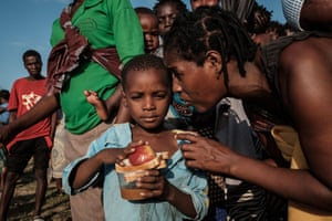 A child listens to his mother after receiving food in Dondo, about 35km north from Beira