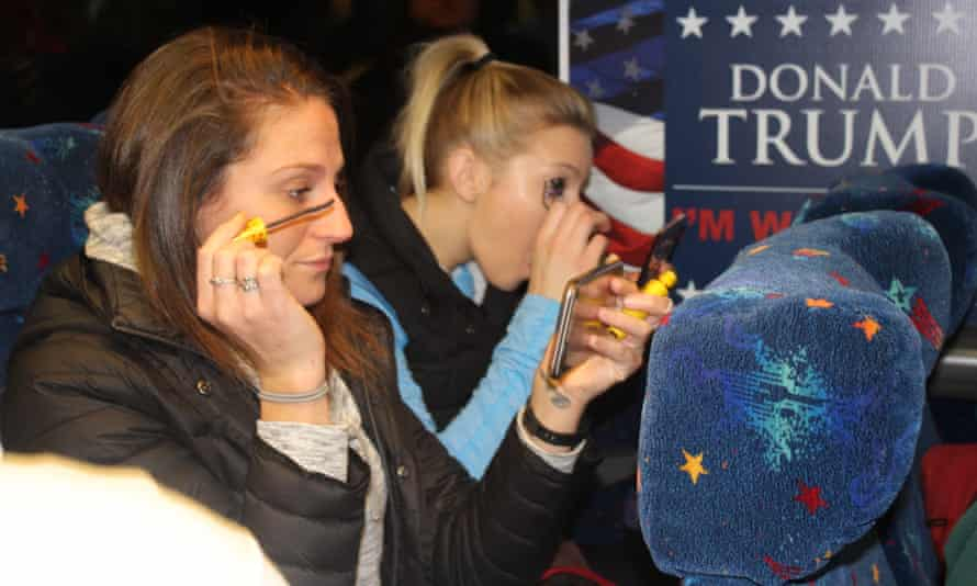 Two friends on an early bus to Trump's inauguration apply their makeup.