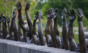 A bronze statue called 'Raise Up', part of the display at the National Memorial for Peace and Justice, a memorial to honor thousands of people killed in lynchings, in Montgomery, Alabama.