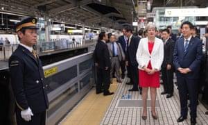Theresa May and Japanese prime minister Shinzo Abe wait at Kyoto railway station for a Shinkansen (Bullet train).