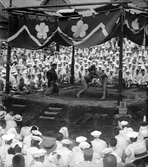 A sumo wrestling match watched by a large crowd of people in the early years of the 20th century