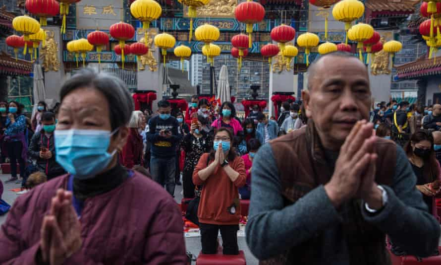 People wear masks as they pray at a temple in Hong Kong
