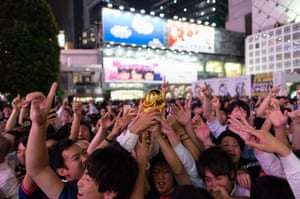 Japanese supporters cheer at a scramble crossing in front of Shibuya Station in Tokyo.