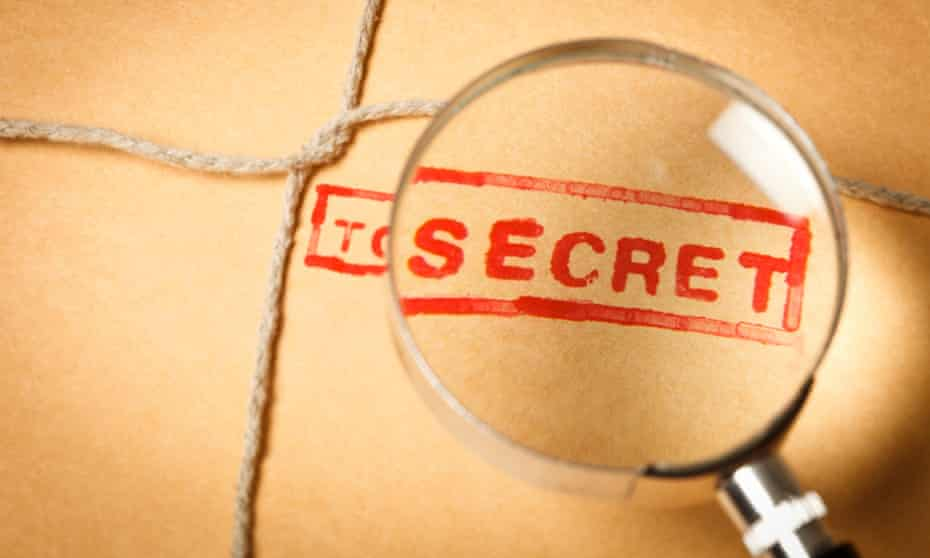 """A magnifying glass over """"top secret"""" stamped on an envelope"""