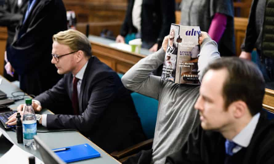 One of the four men on trial holds a magazine in front of his face in the courtroom in Berlin.