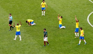 The final whistle goes and Brazil players celebrate victory as Mexico's Carlos Vela looks dejected.