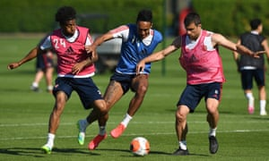 Reiss Nelson (left) and Sokratis Papastathopoulos try to dispossess Pierre-Emerick Aubameyang during an Arsenal training session at London Colney.