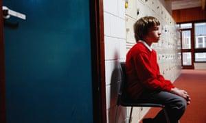 Schoolboy sitting on chair in corridor