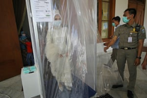 Surabaya, Indonesia: a bride wearing a mask is sprayed inside a disinfection chamber